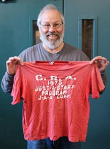 CITC Donor Mitch Goldstein, showing off his 1975 JAS/Cambridge Redevelopment Authority t-shirt given to him as a VISTA Attorney working at Consilio Hispano de Cambridge on Columbia Street